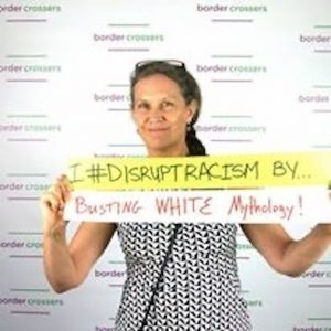 Debby holding a sign that says Disrupt Racism by Busting White Mythology