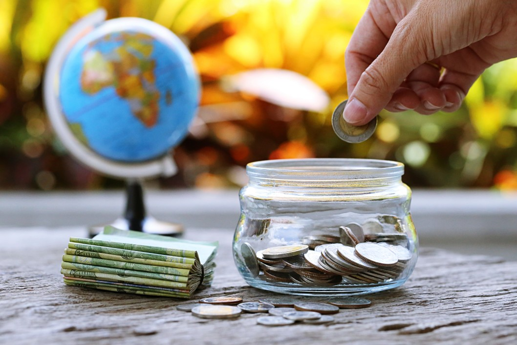 People putting coins in glass jar and money bank with a blurry world globe map closeup in the background